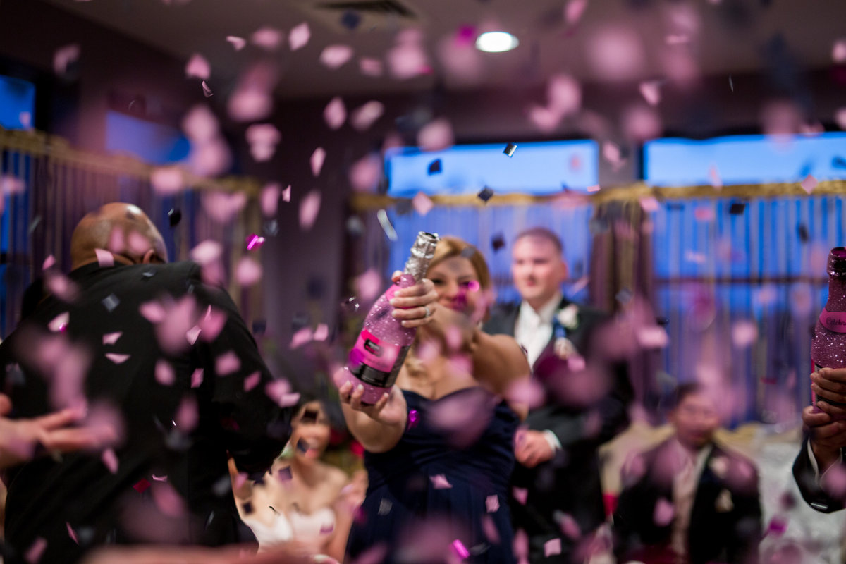wedding party pop confetti champagne bottle after ceremony to celebrate bride and groom at Granberry Hills Event Center