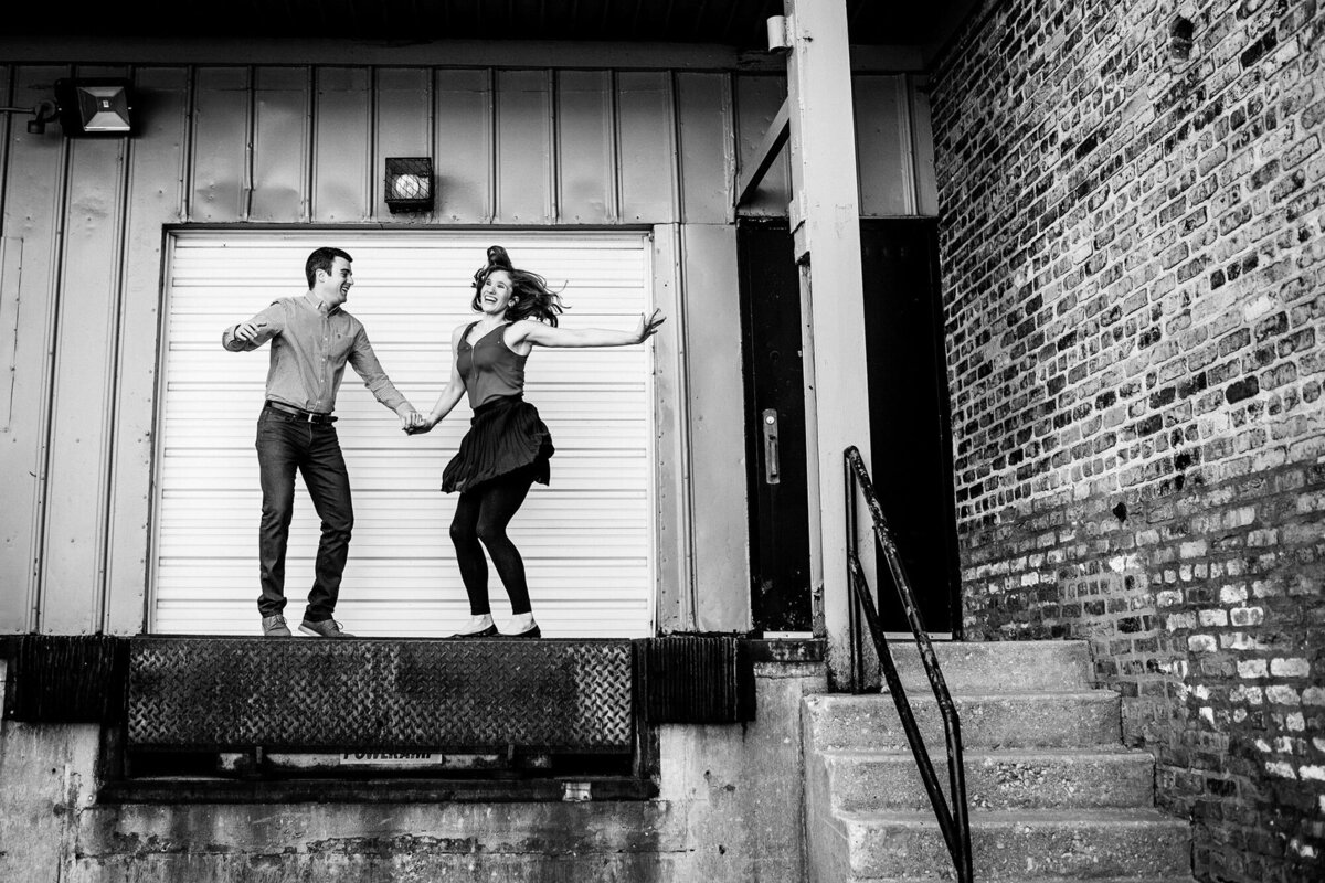 A couple jumps for joy during a West Loop engagement session.