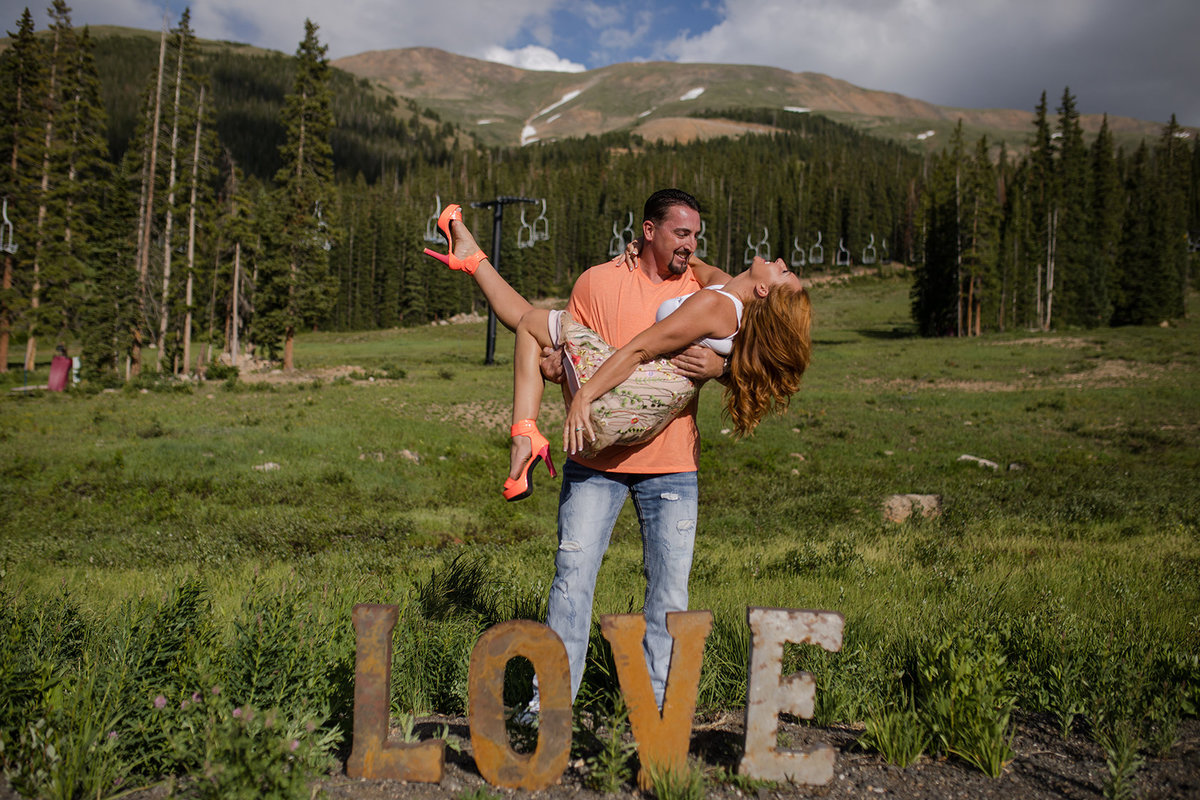 Love sign with engaged couple in mountains