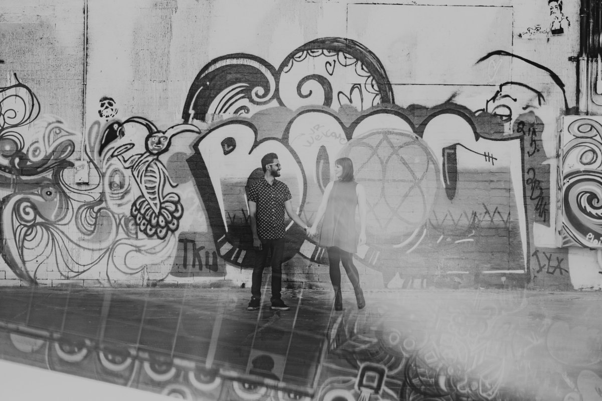 Reno engagement pictures couple holds hands in front of graffiti wall