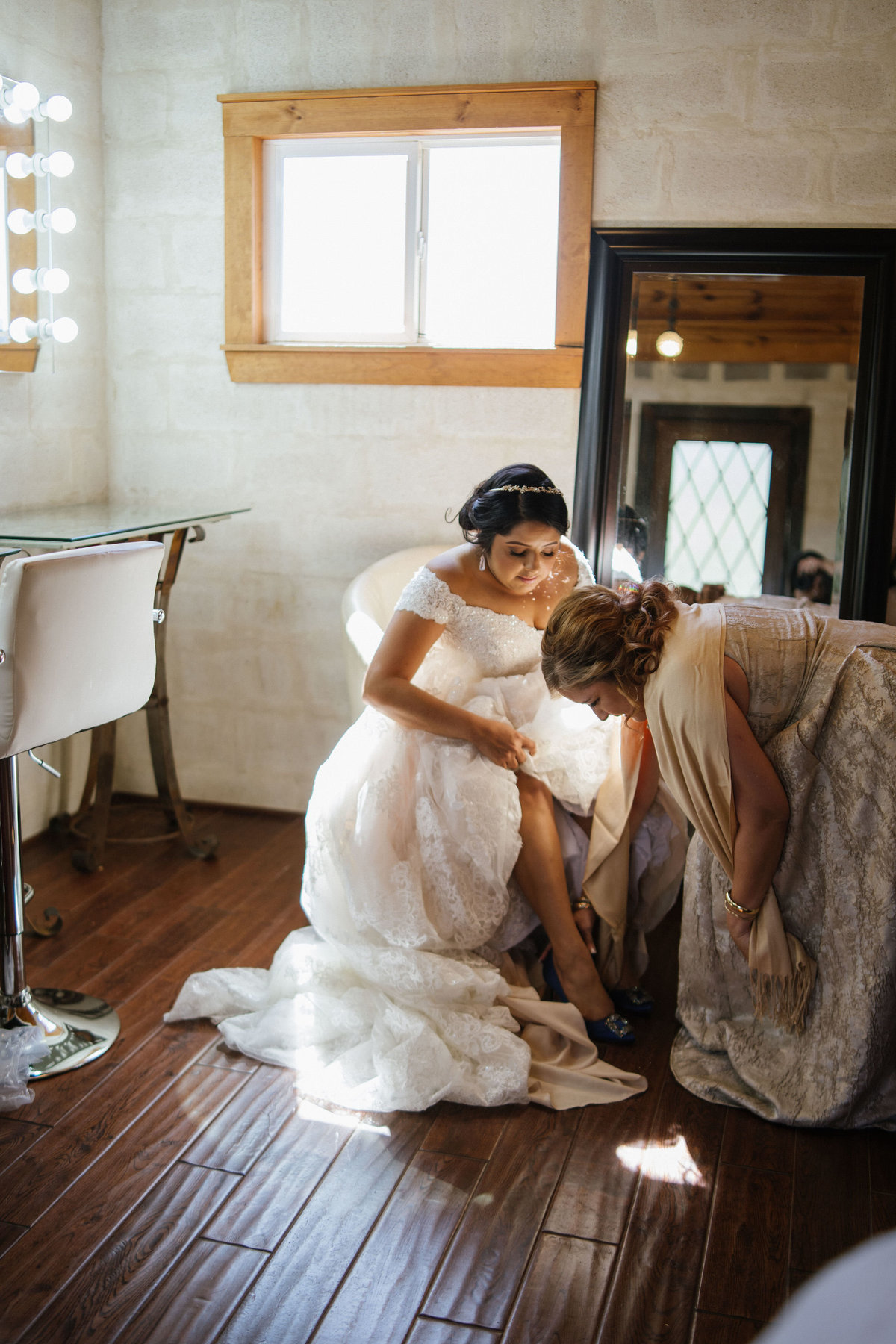 Mother of bride helping daughter put on her wedding shoes during getting ready for ceremony at Oaks of Heavenly venue