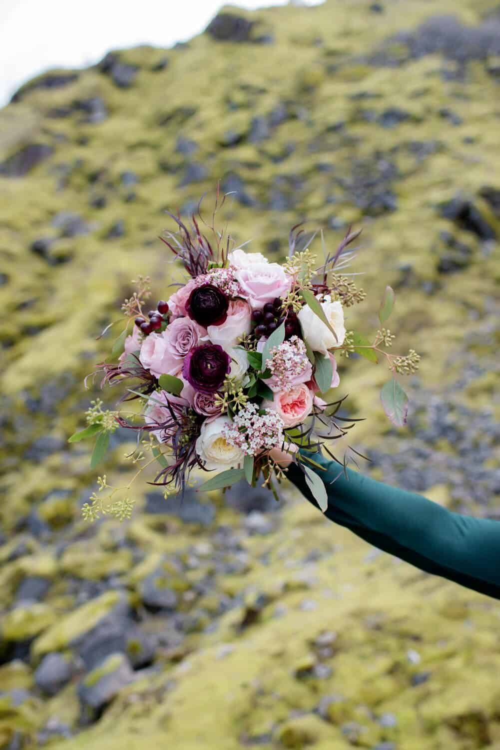 a photo of an extended arm holding a pretty pink and burgundy bouquet by flowers by alana