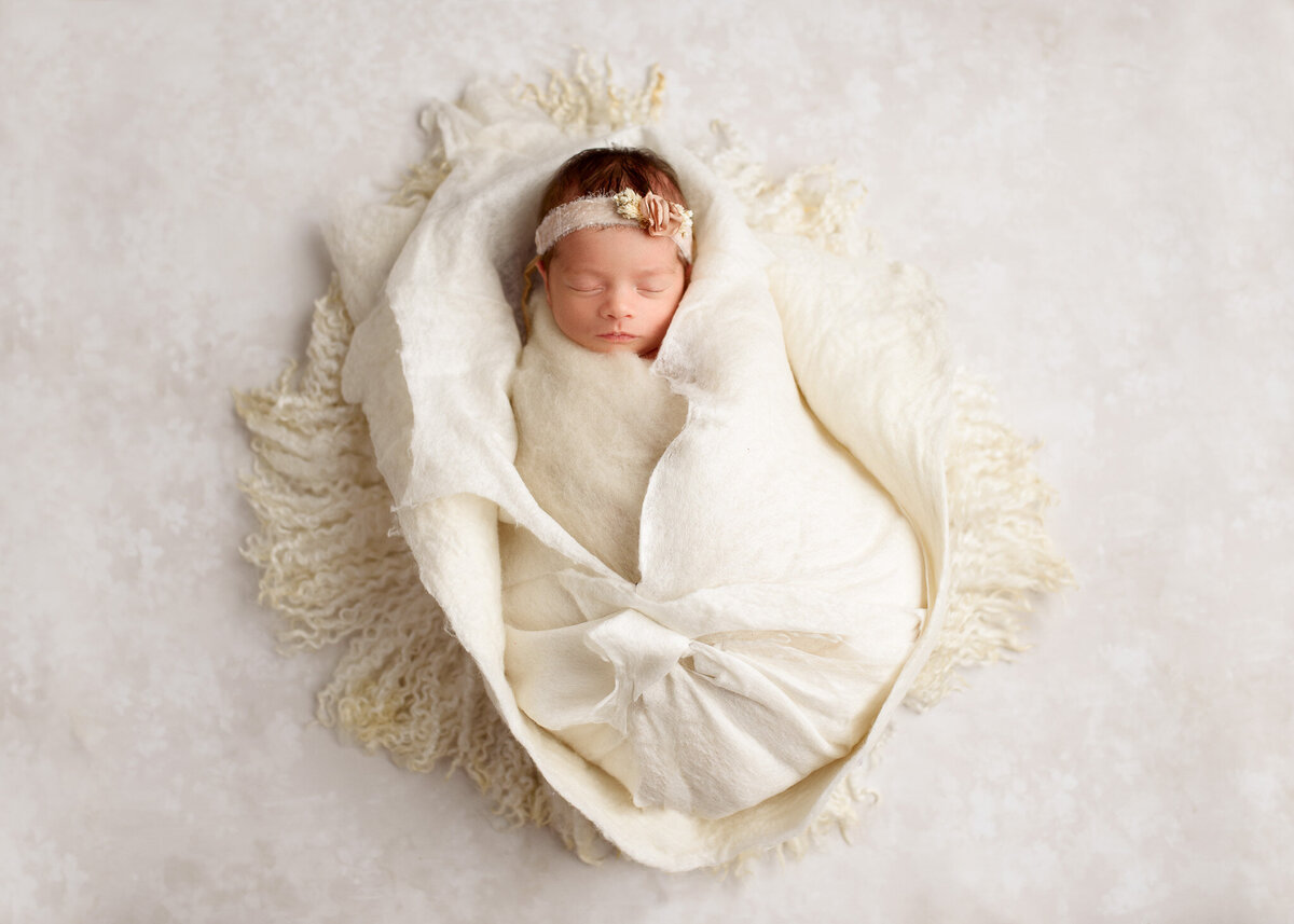 Newborn baby wrapped like flower in cream