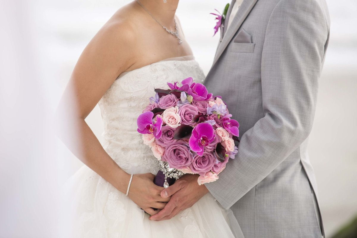 Bride and groom holding a bouquet of pink and purple flowers at Bridgeview Yacht Club