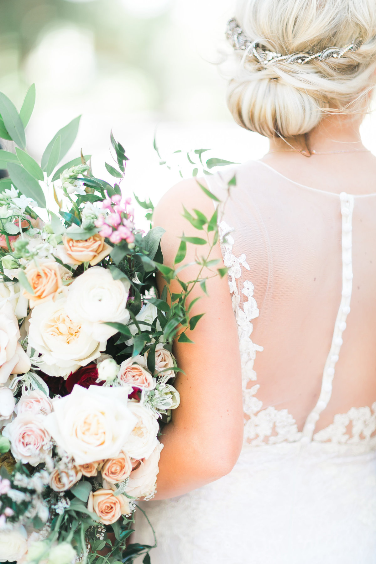 bridal updo and back of wedding dress details with bridal bouquet