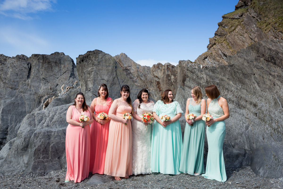 bridesmaids on beach at tunnels beaches colourful dresses