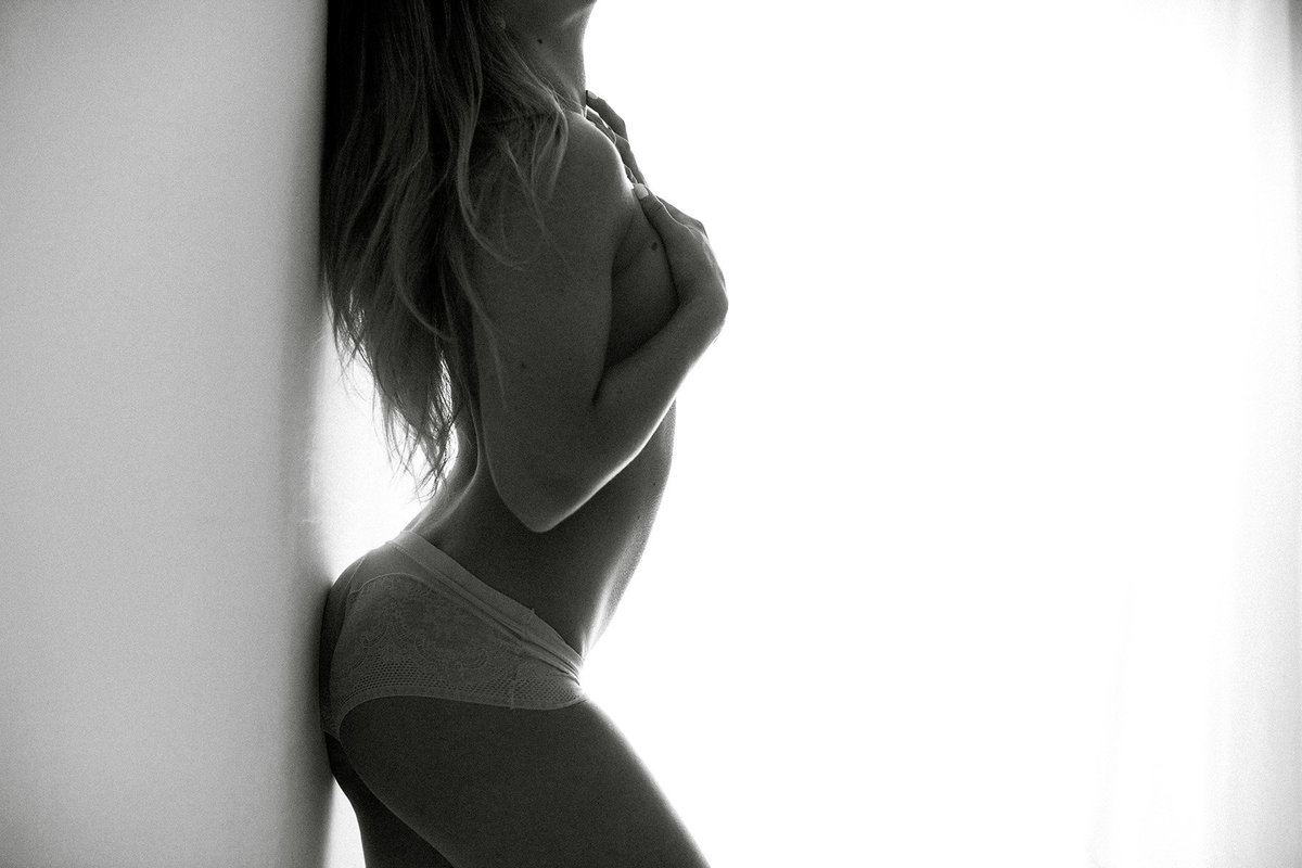 black and white image of woman against wall during boudoir session