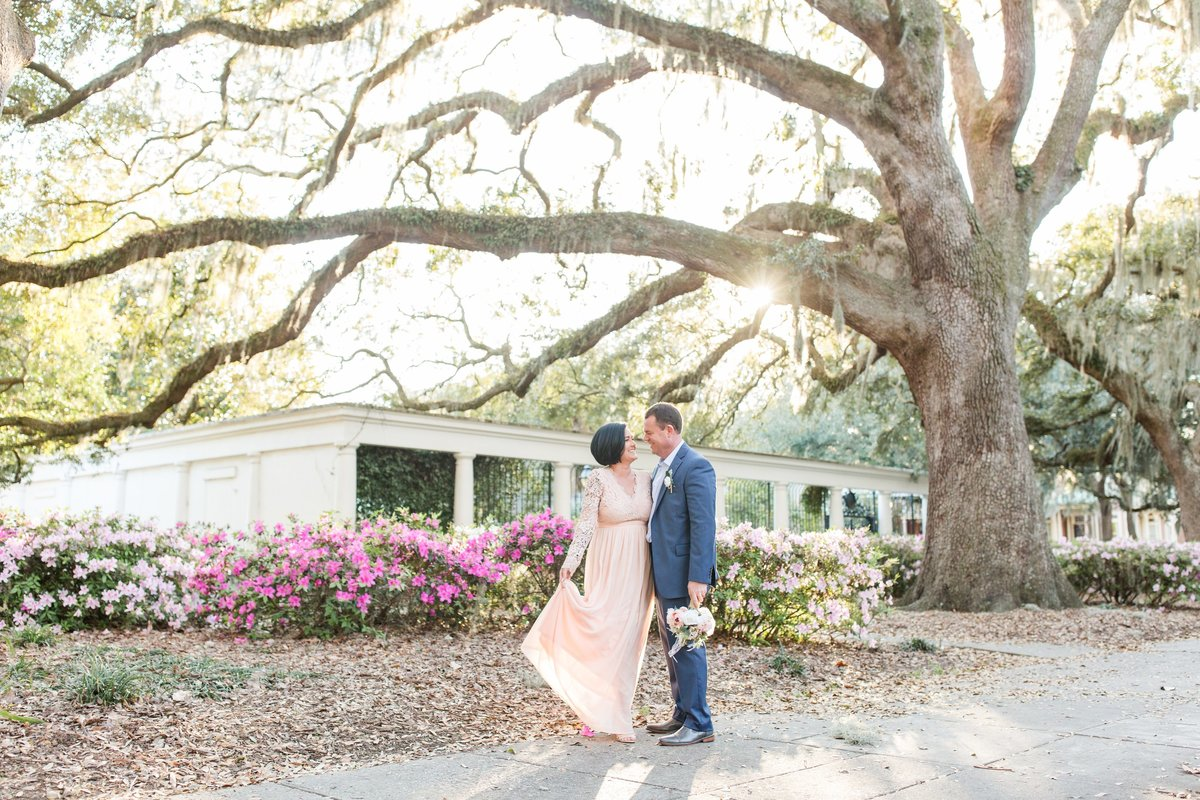 bride ang groom standing under an oak tree with azaleas blooming in forsyth park savannah