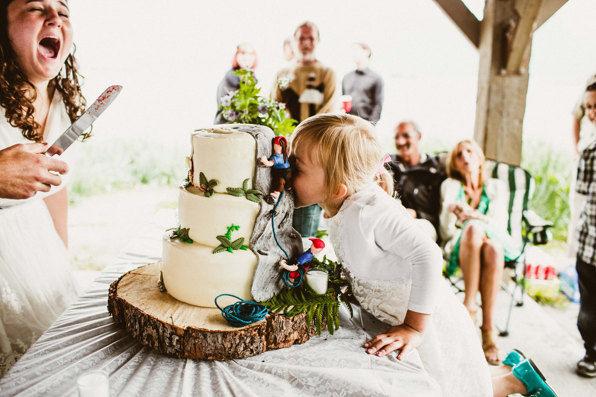 flower girls takes bite of uncut cake in valdez wedding