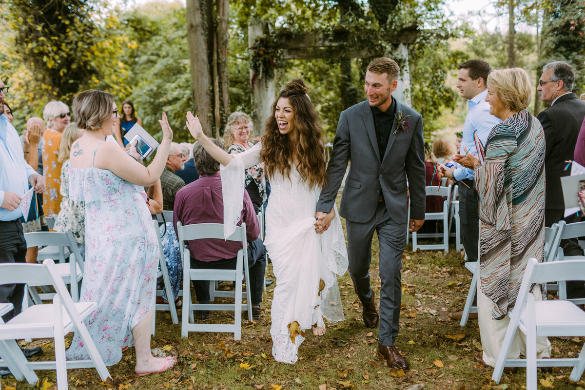 couple walking out of wedding ceremony barefoot
