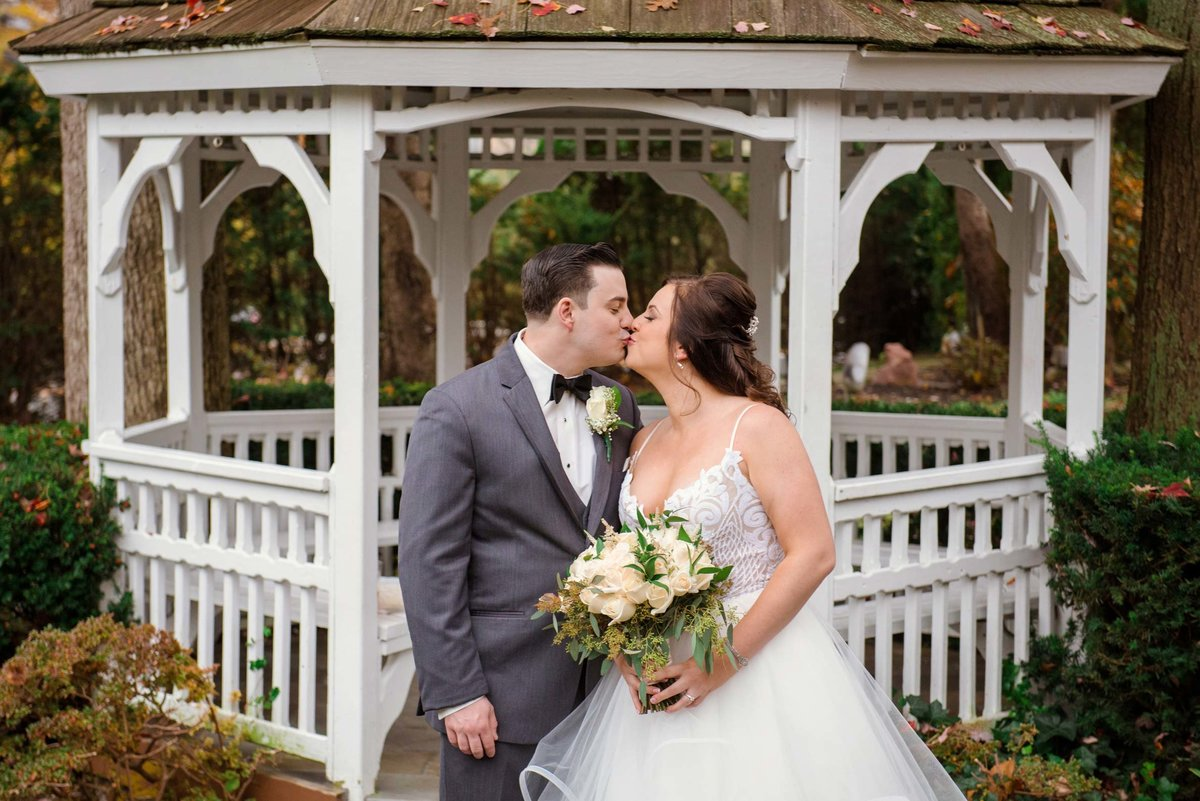 Bride and groom kissing infront of the gazebo of Fox Hollow