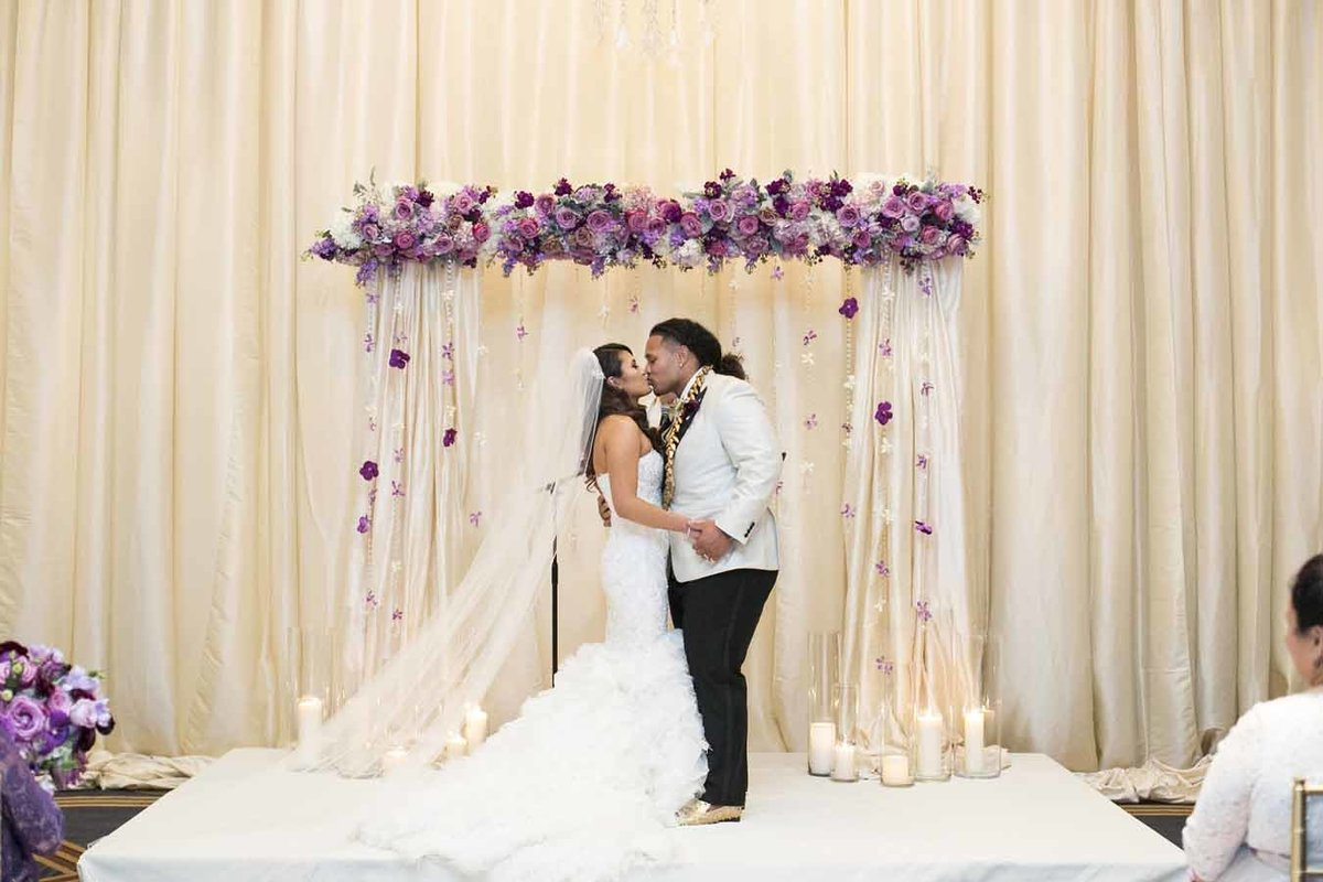 Beautiful ceremony arch with dangling strands of crystal and orchids frame the couple.