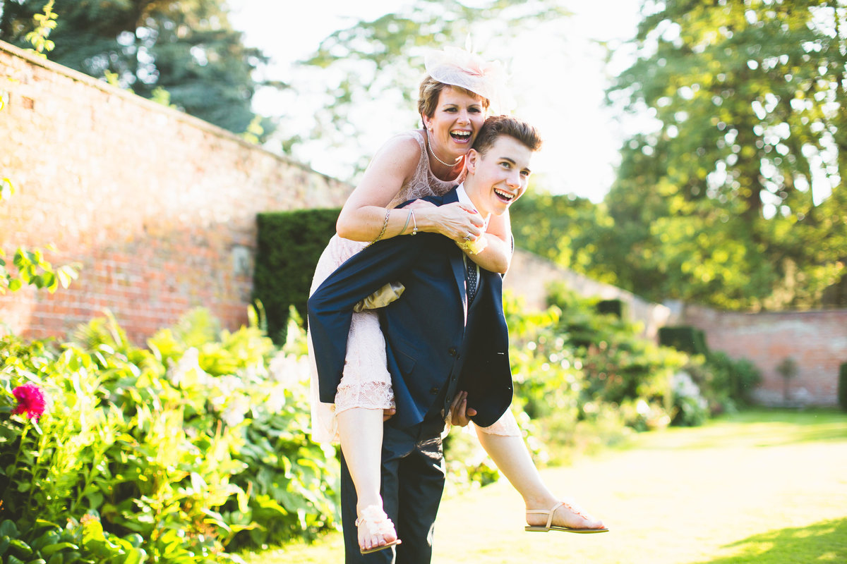 bridesmaid having piggy back at wedding