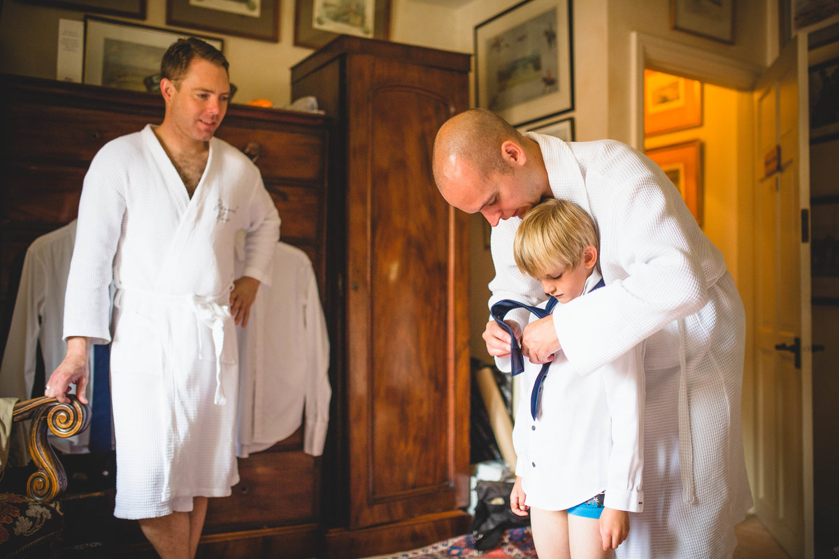 groom and best man helping son get ready for wedding