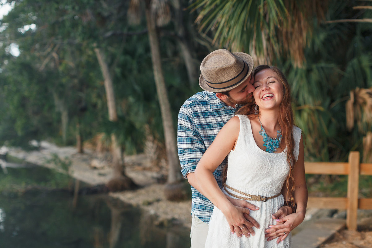 Groom in a Fedora Embraces his Fiance from Behind and Kisses her During their Washington Oaks Engagement Photo Session