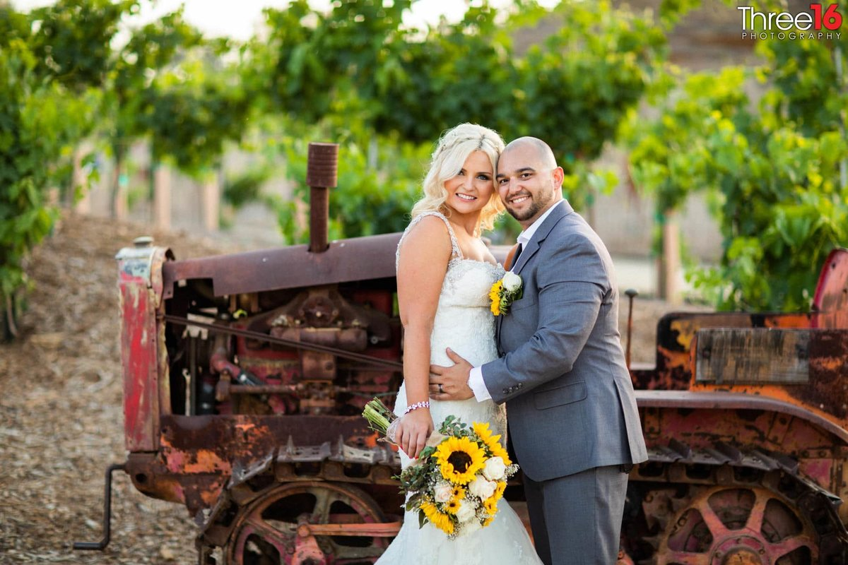 Bride and Groom pose in front of an old tractor