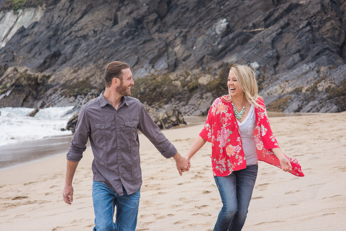 Young couple holding hands and wearing denim, laughing while running on the beach in Kerry