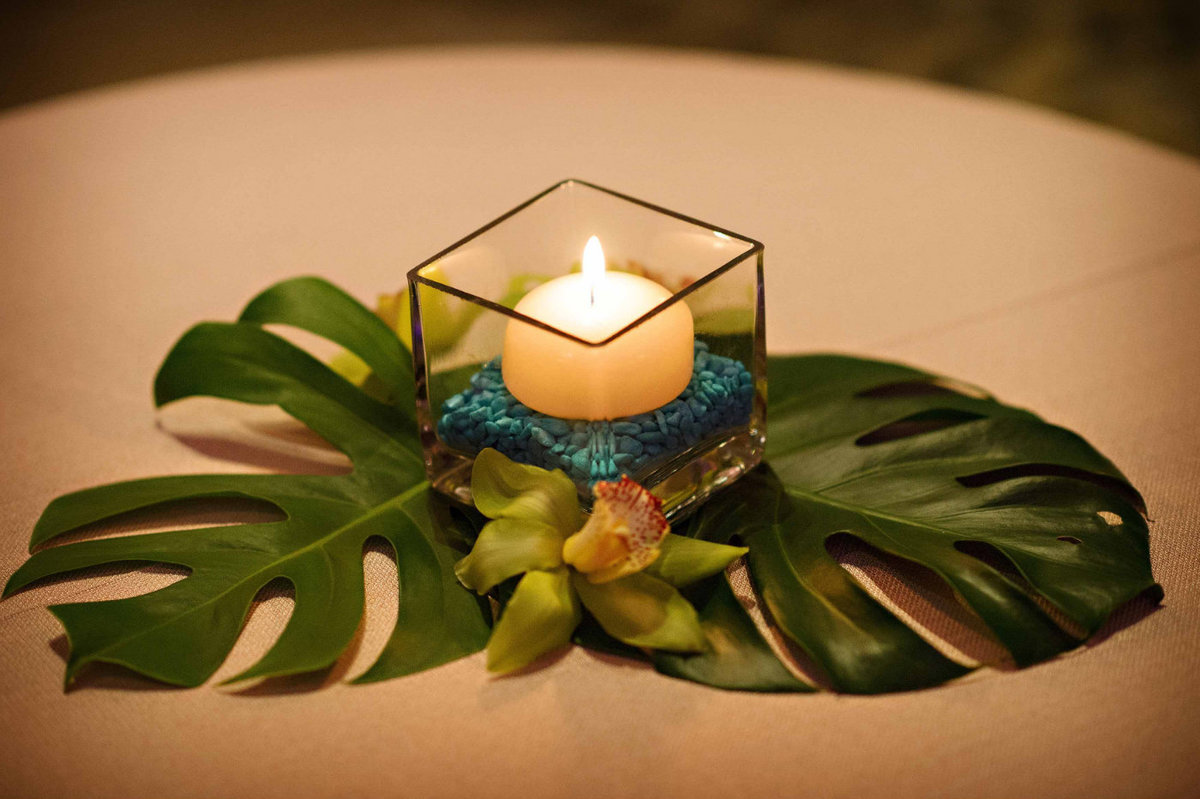 votive candle on monstera leaves tropical theme