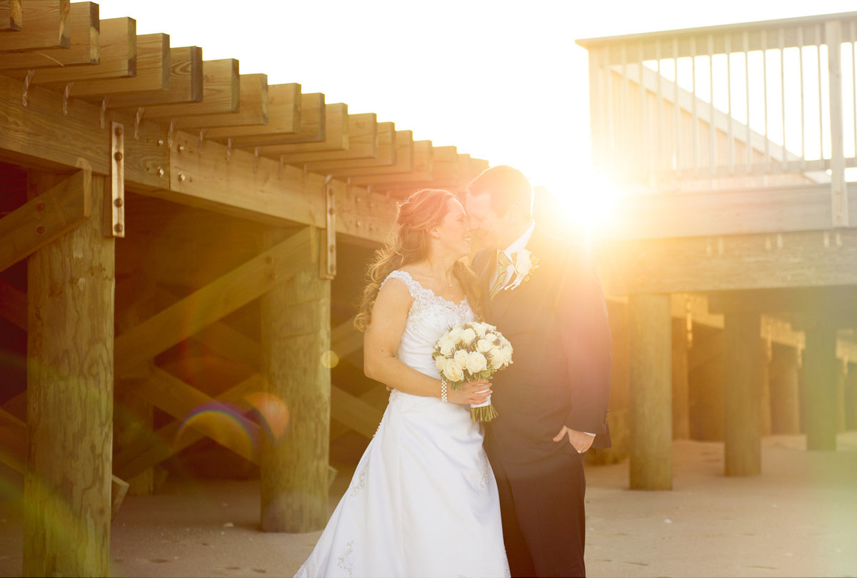 bride and groom with sunflare under boardwalk