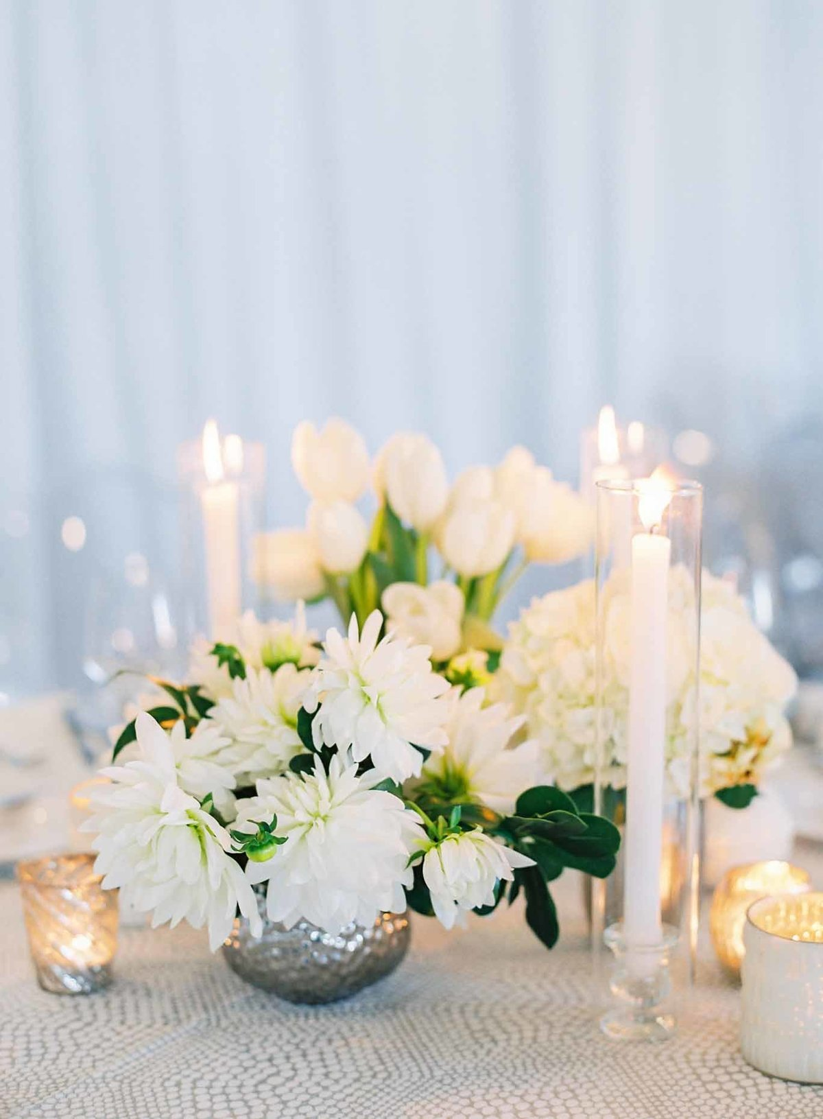 Small silver vases of white dahlias and tulips are paired with tall taper candles here beautifully.