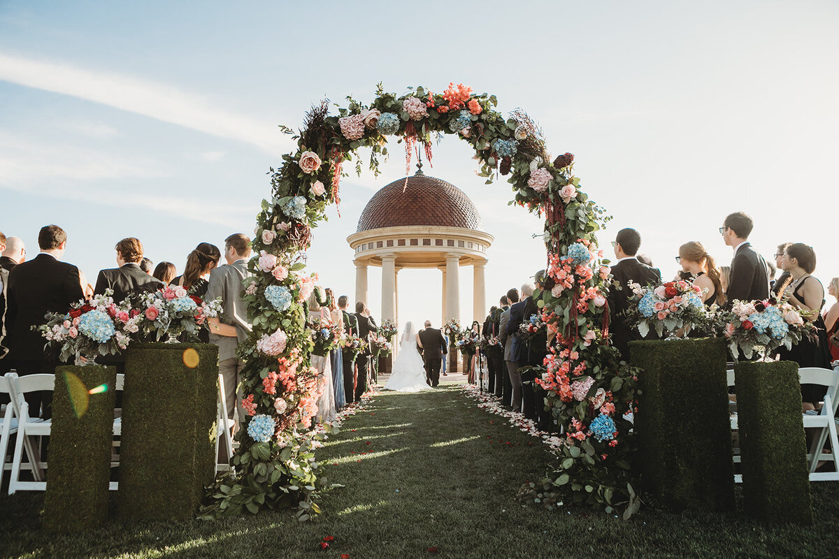 Indianapolis photographer at the Resort at Pelican Hill shooting a gorgeous wedding under a gazebo through a flower arch