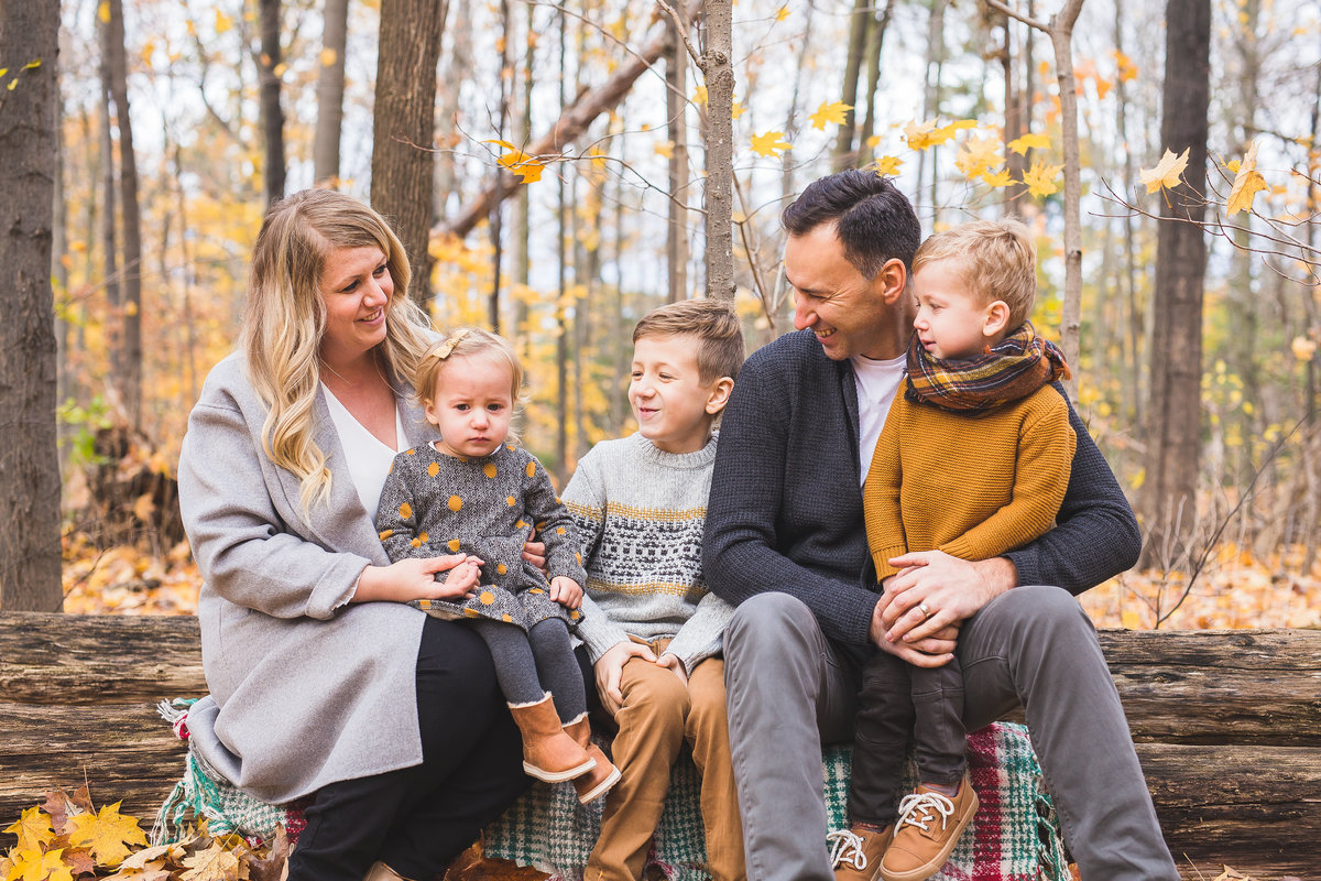 Family of 5 sitting on logs in woods interacting {Oakville Family Photographer}