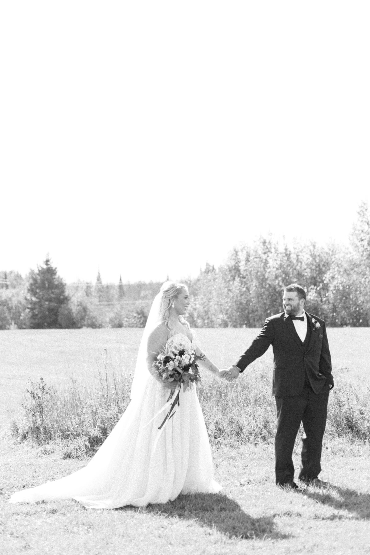 A groom leads his bride through the field behind the Norwester Hotel in Thunder Bay