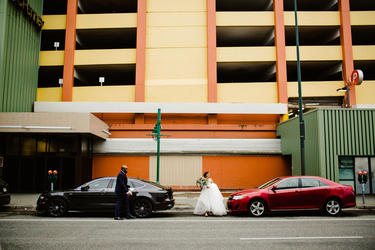 wedding couple crosses street in front of colorful parking garage in downtown anchorage