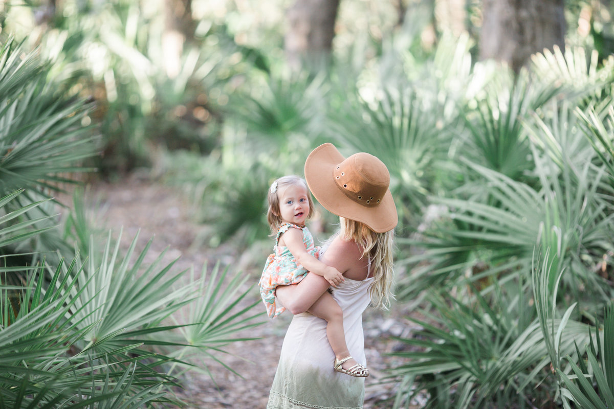 Jacksonville Family Photographer photo of a mother holding her toddler daughter infront of palm fronds