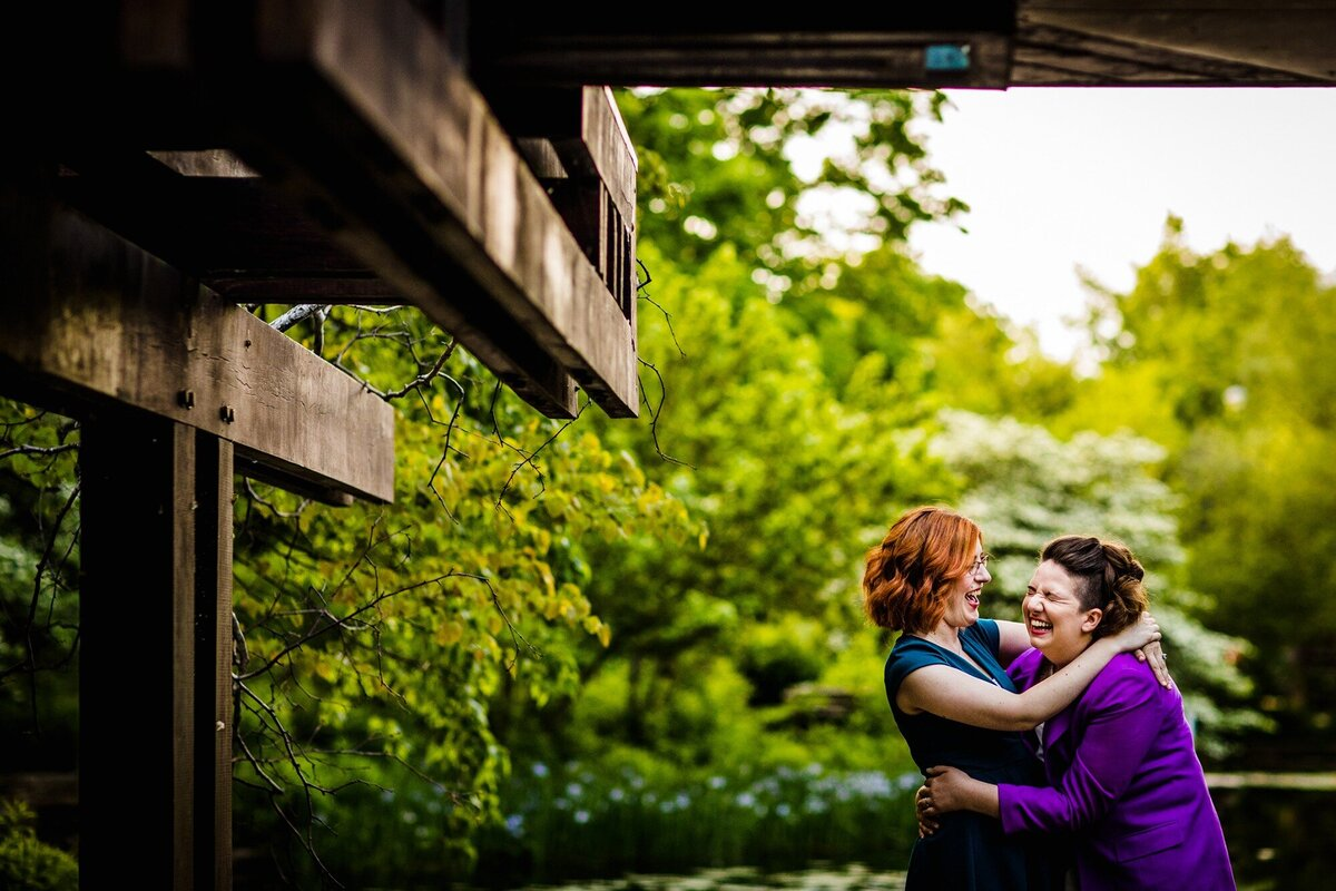 A couple laughs together during a Caldwell Lily Pond engagement session.