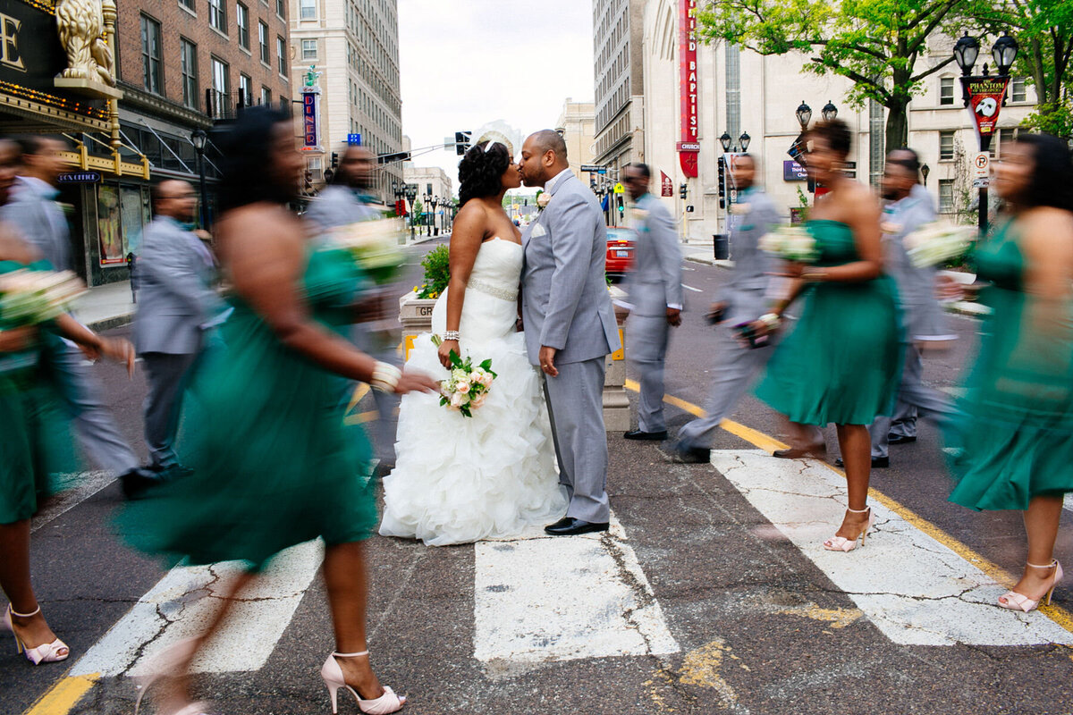 Bridal party members cross the street, blurred from movement, as the bride and groom hold still in downtown St Louis.