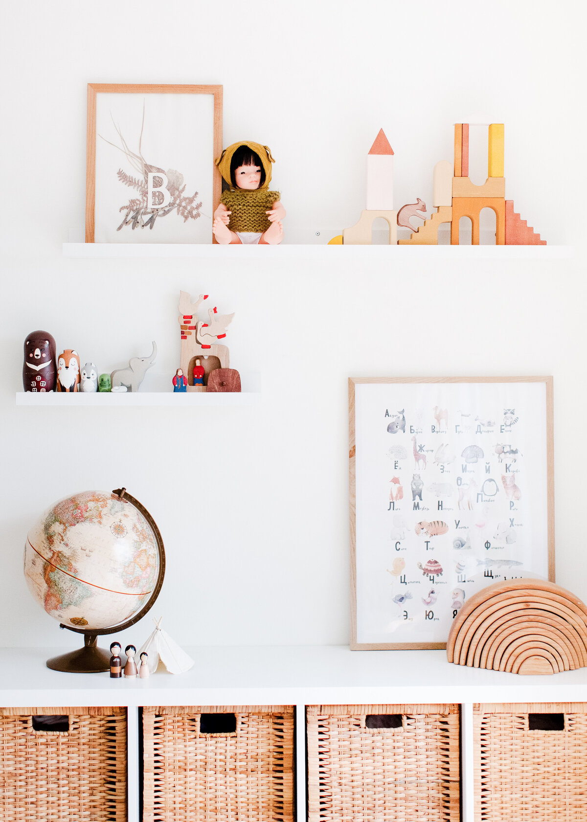 A boho sideboard with rattan baskets holds a globe against a white wall with shelves in a children's playroom.