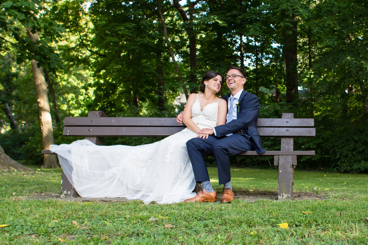 Bride and Groom on bench lace wedding dress