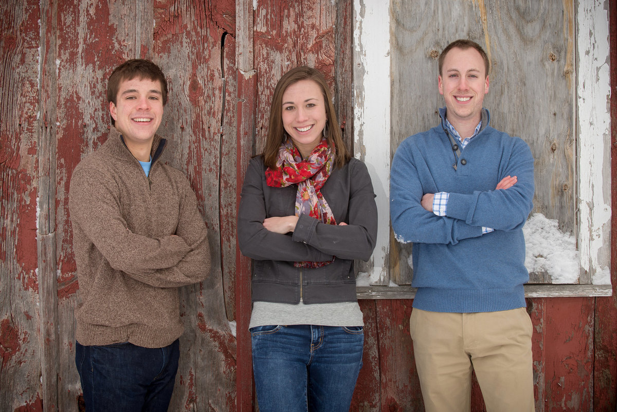 Young adult during winter family portrait in front of a  historic red barn in Leroy Oaks forest preserve
