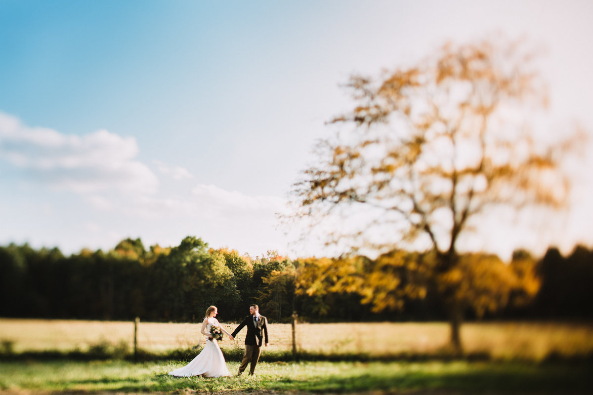 a photo of a couple running through the countryside at Jorgensen Farms