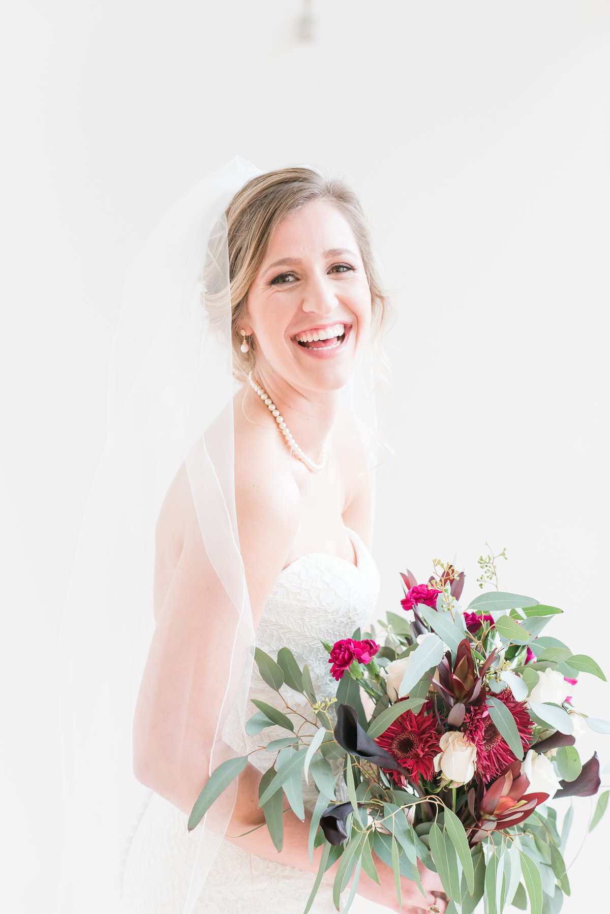 A bride wearing a strapless dress with cathedral length veil holding red and green wedding bouquet in front of a white wall smiling at the camera at the Glass Box at 230 in Raleigh