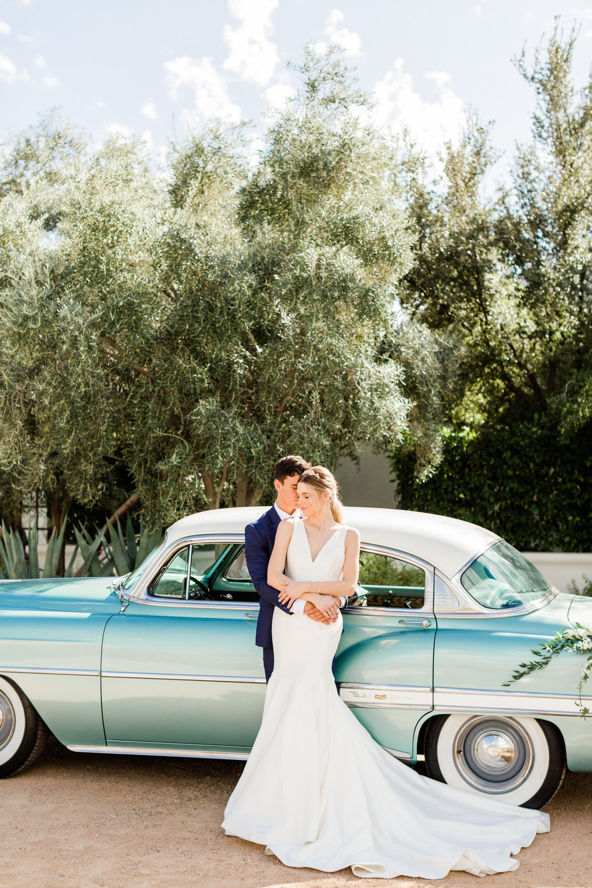 newlywed couple posing in front of a classic teal blue car