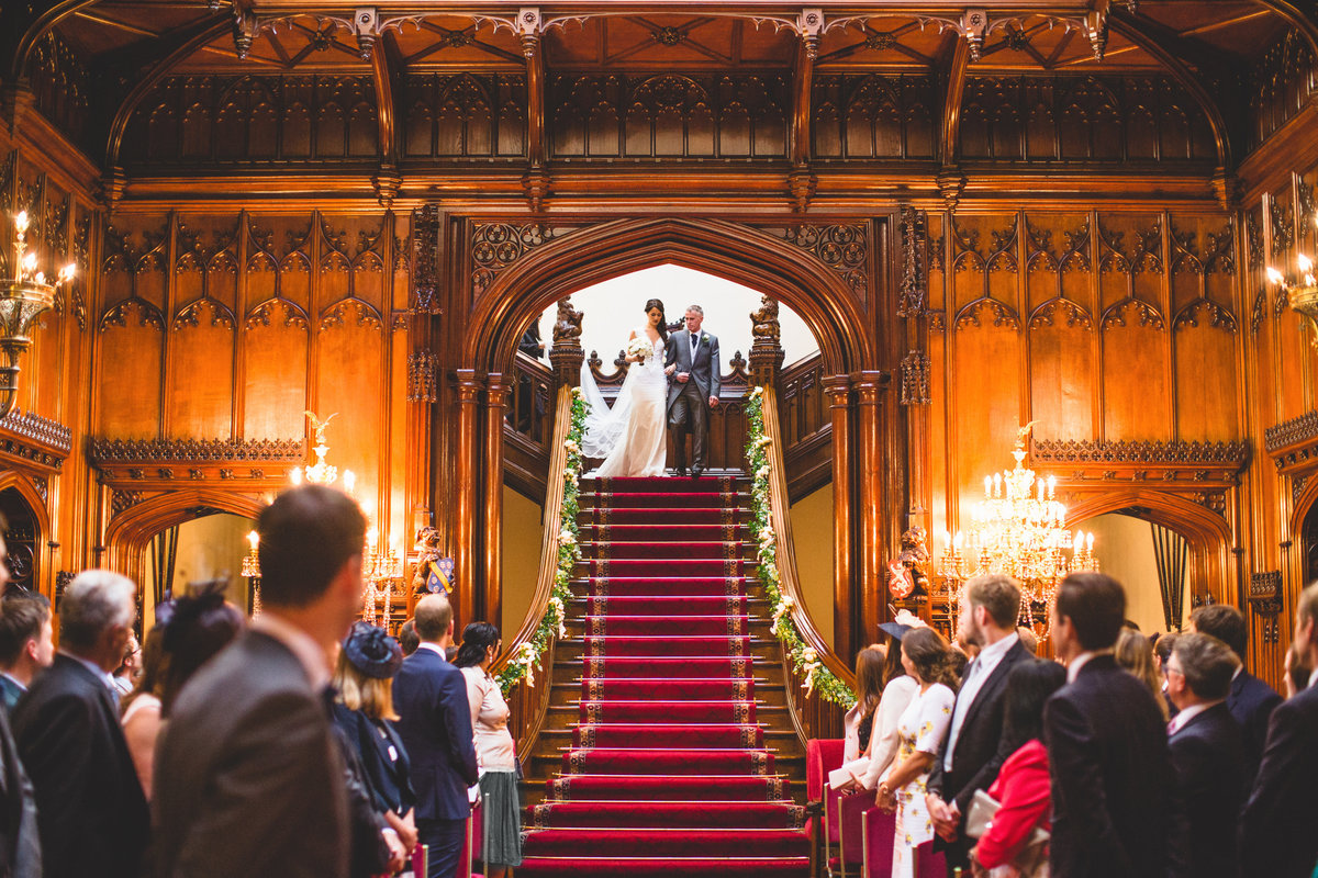 bride coming down the stairs into the wedding ceremony at allerton castle