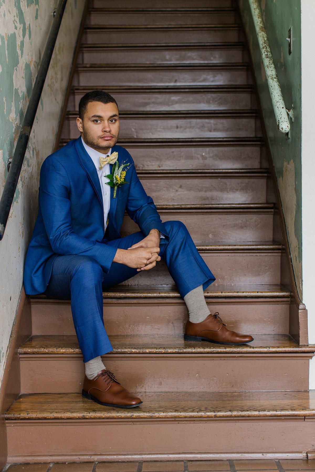 groom-navy-suit-brown-shoes-stairs-yellow-bowtie