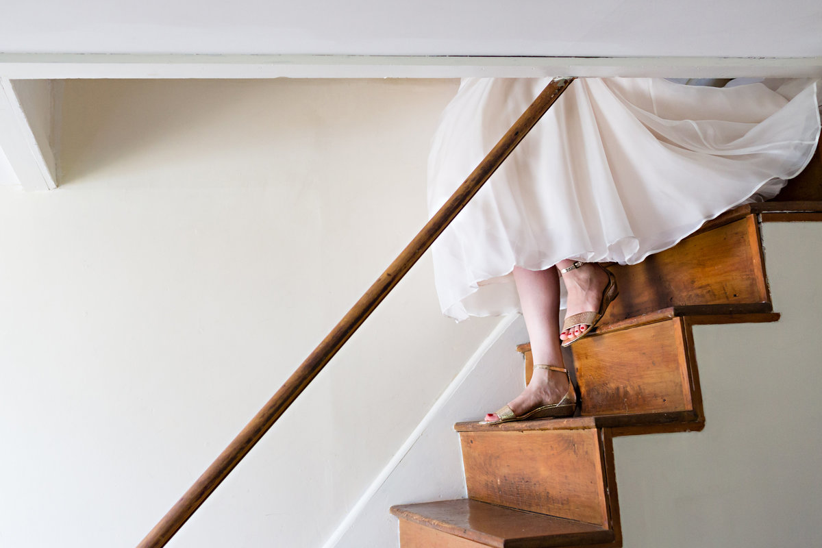 The bride comes down the stairs for the ceremony at Shady Lane Farm  Maine wedding