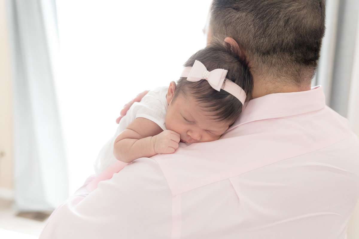 Dad cuddles sleeping  newborn daughter on his shoulder