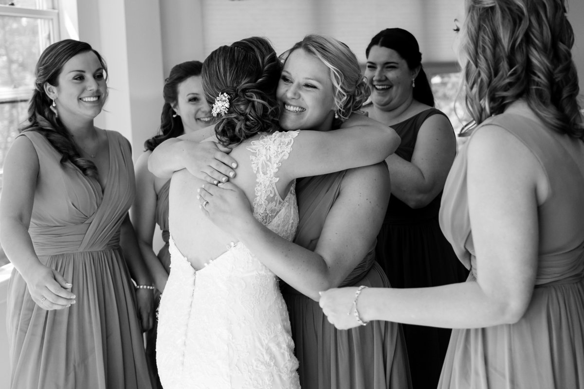 The bride is hugged by her bridesmaids while they get ready for the ceremony at Waterville Valley Resort NH