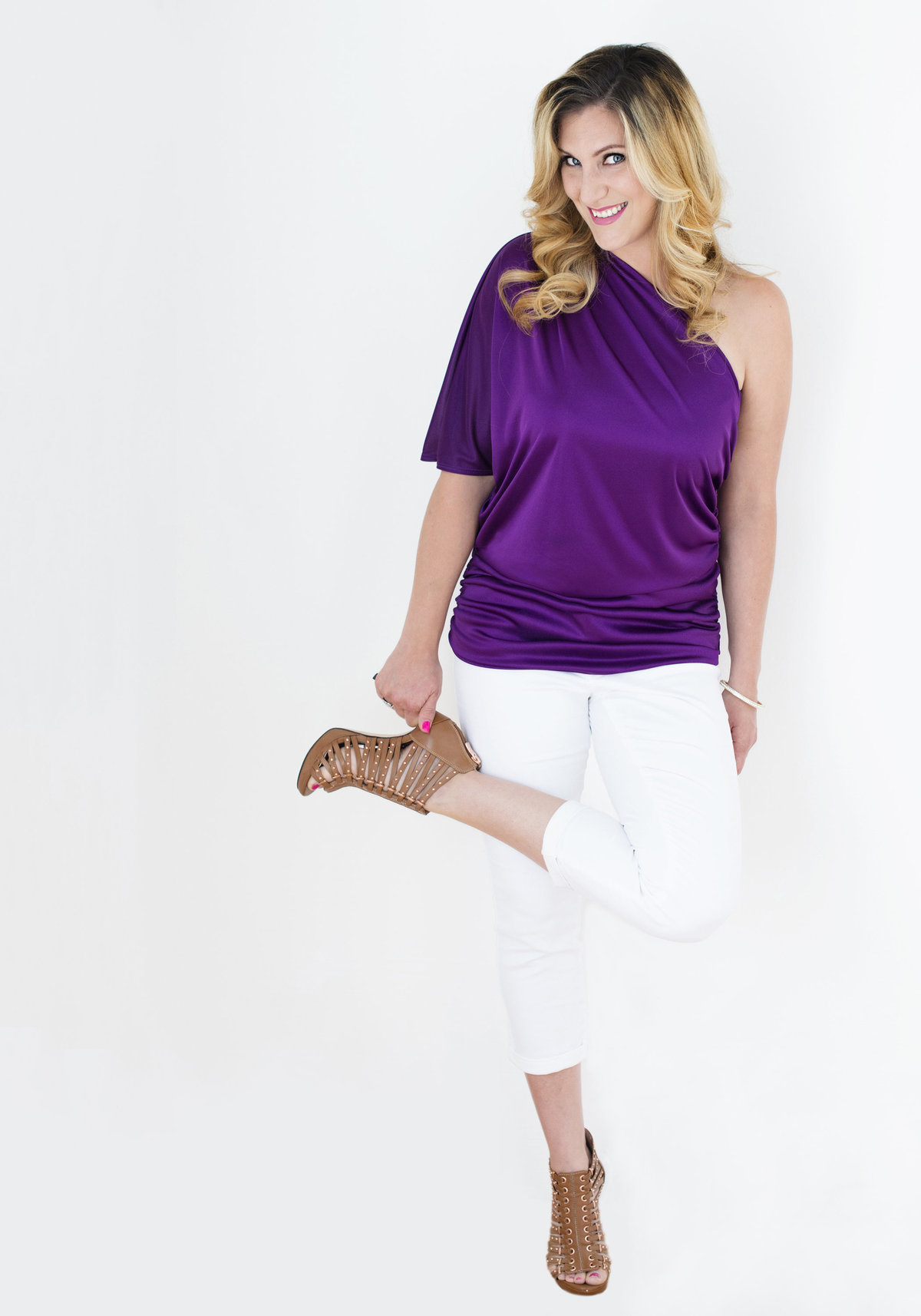 personal branding headshot of  social media strategist with  one  leg folded wearing purple color  top  full length  shot at  photo studio