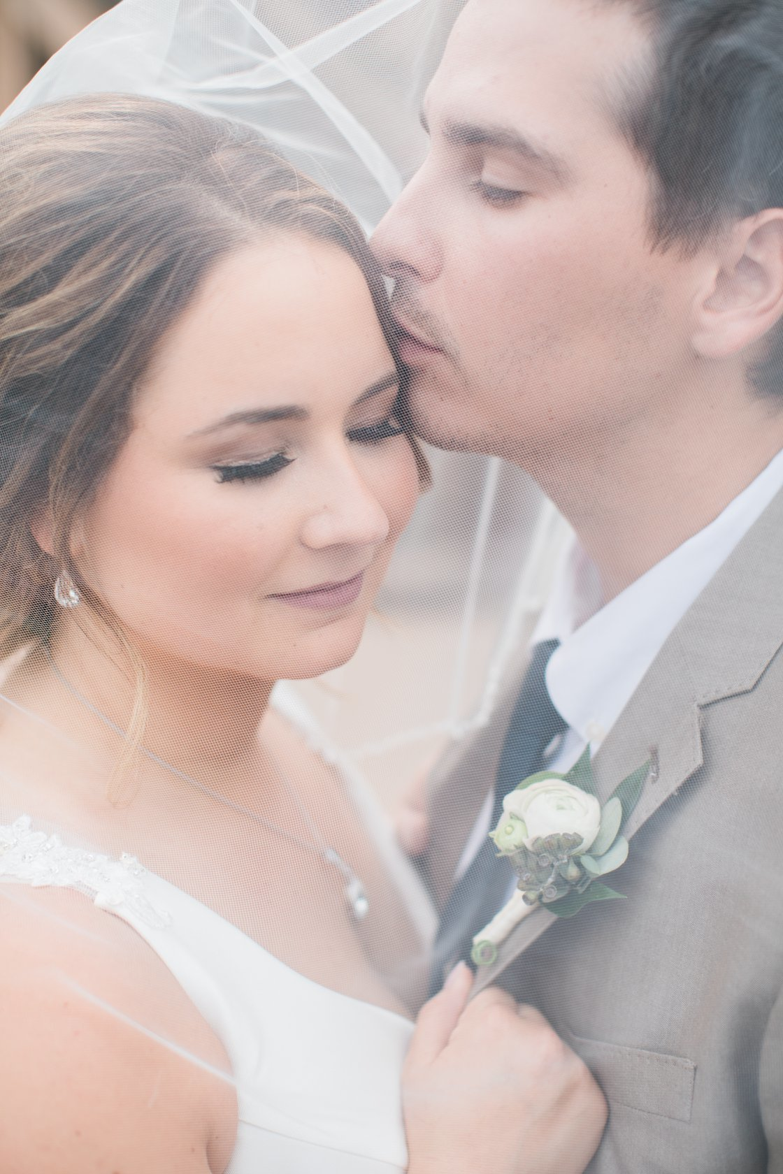 Wedding Photographer, groom kissing bride's forehead under veil