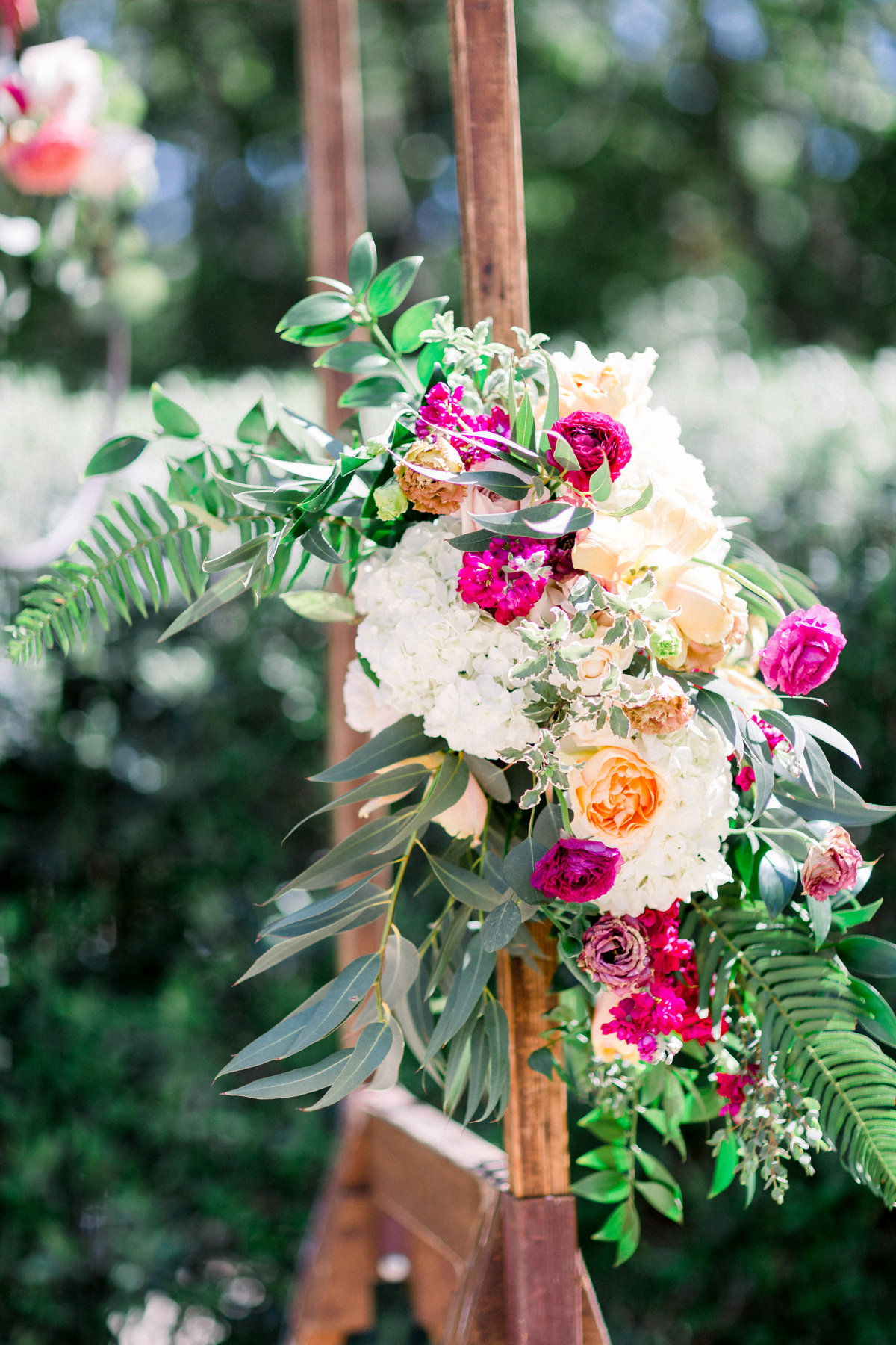 Wedding ceremony arch floral with mauve and orange flowers at Maravilla Gardens
