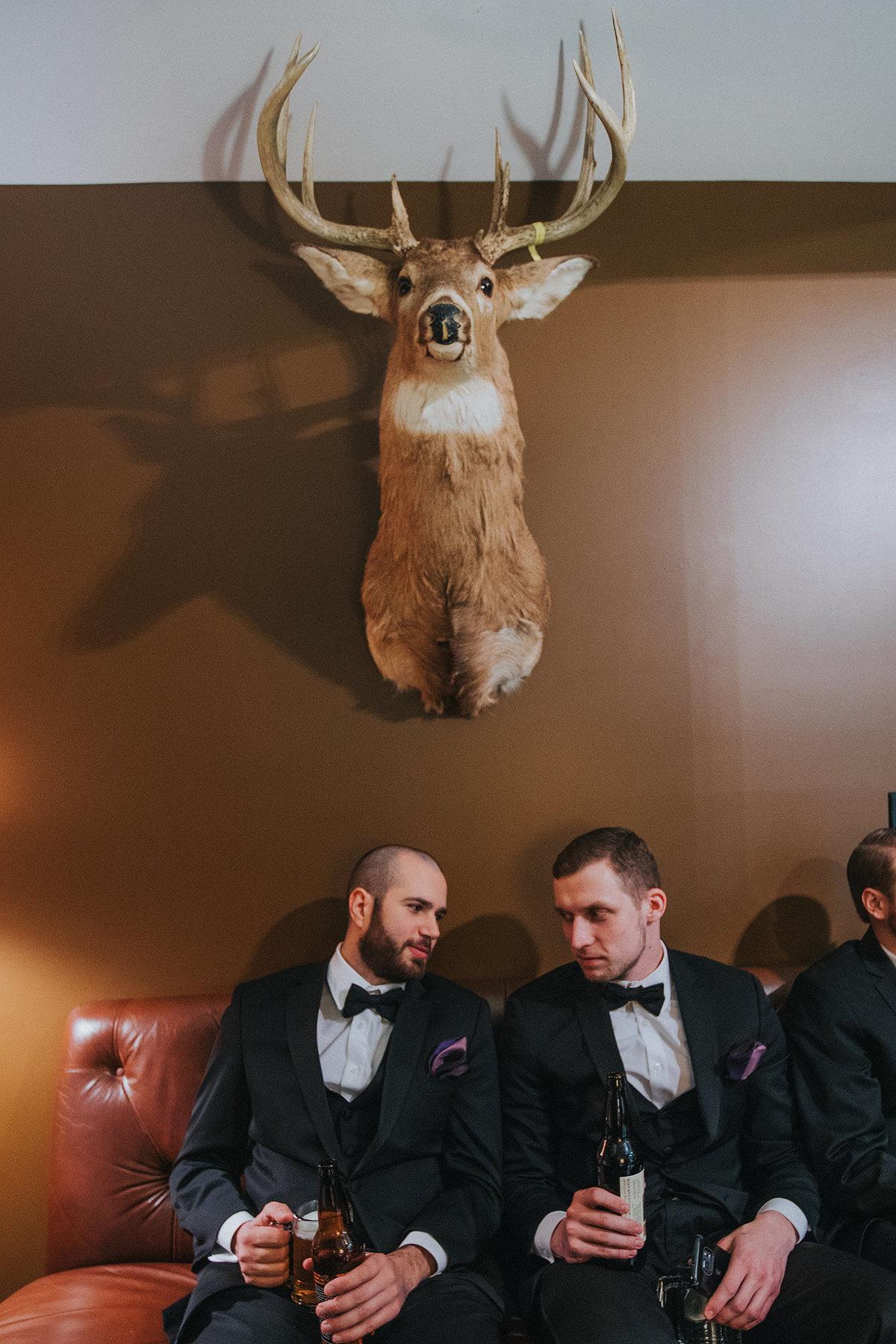 groomsmen talking under mounted deer