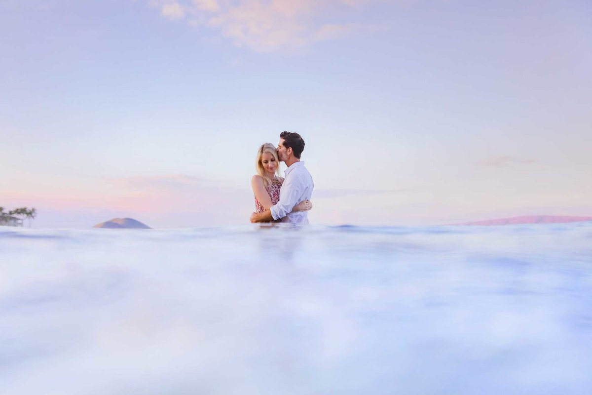 Man kissing woman on the forehead in the ocean on Maui, Hawaii