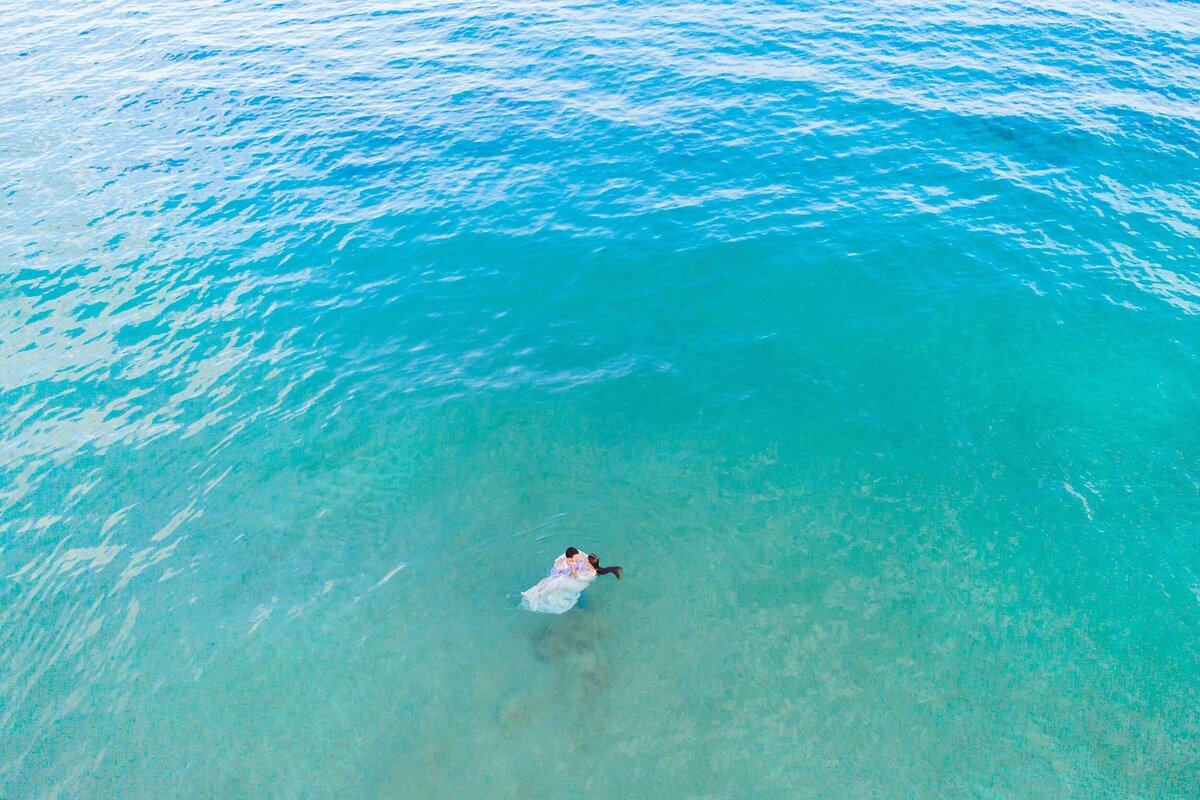 Recently engaged couple floats in the ocean while being photographed by drone on Maui