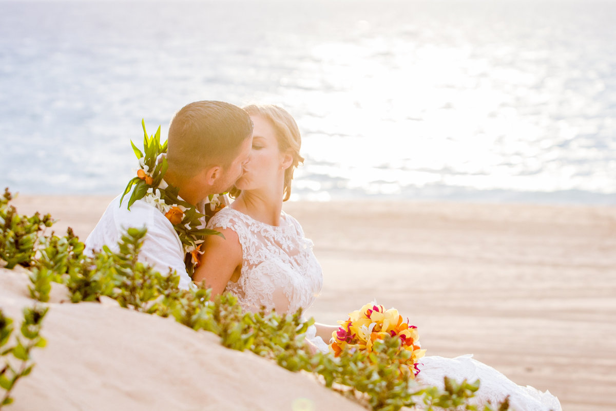 Kisses on the beach during Kauai wedding elopement.