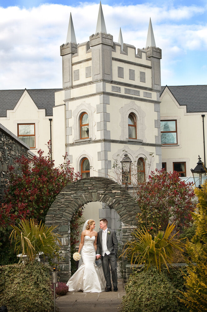Bride in satin, mermaid style wedding dress, holding a white bouquet while walking with her groom in a grey tailcoat and white tie at the Muckross Park Hotel in Kerry